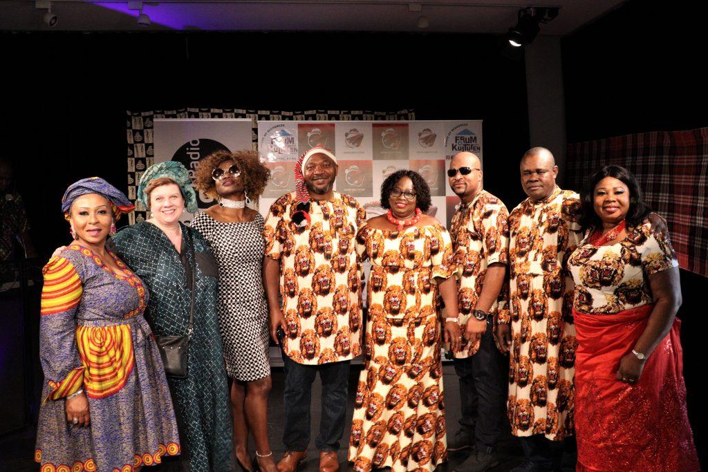 Mehrere Schwarze und weiße Frauen und Männer lachen in die Kamera und präsentieren ihre Kleidung aus afrikanischen Stoffen.